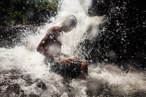 A man sits beneath a waterfall in Koh Kong Cambodia.