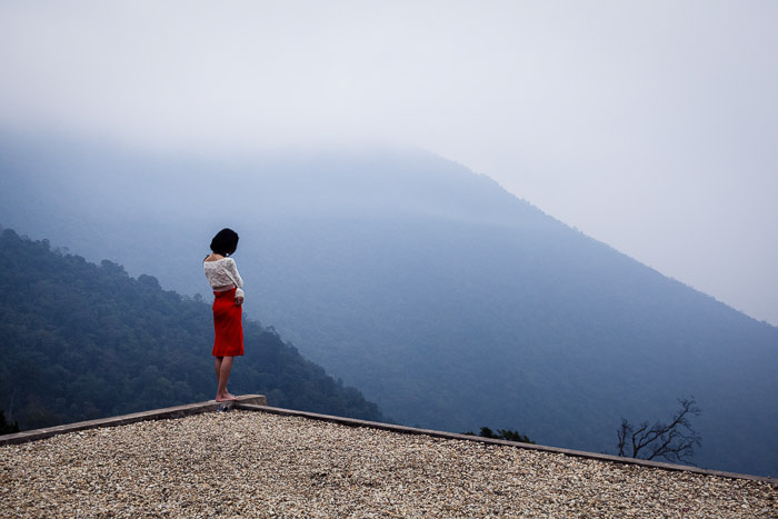 A young woman on the edge of a house in Vietnam.