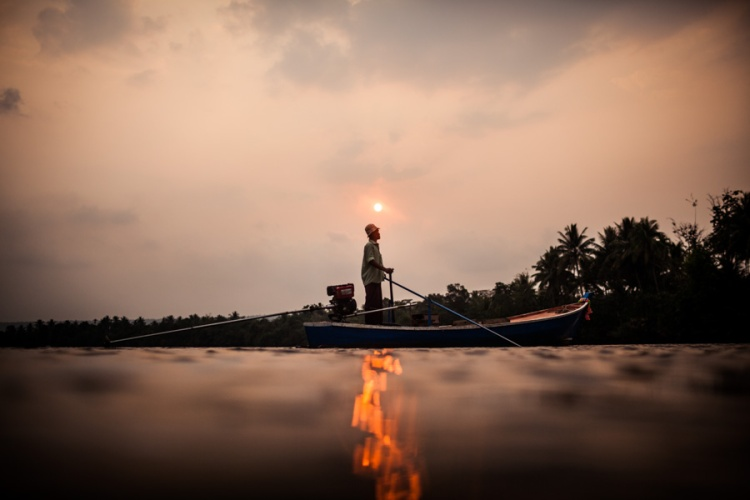 A fisherman rows his boat on the Tatai river at sunset, in Koh Kong, Cambodia.