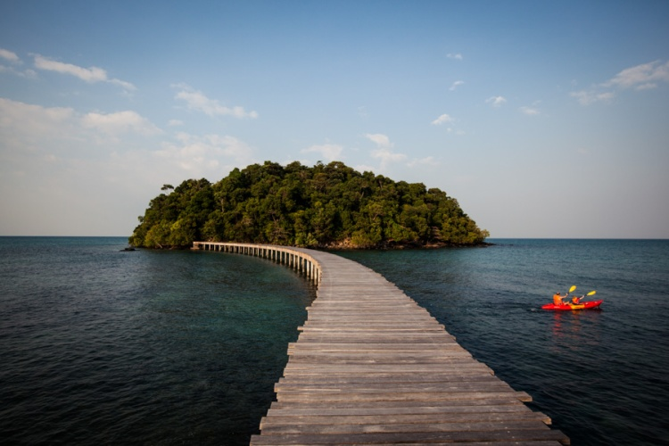 A kayak glides past an over-water walkway at Song Saa resort, on a private island off the coast of Sihanoukville, Cambodia.