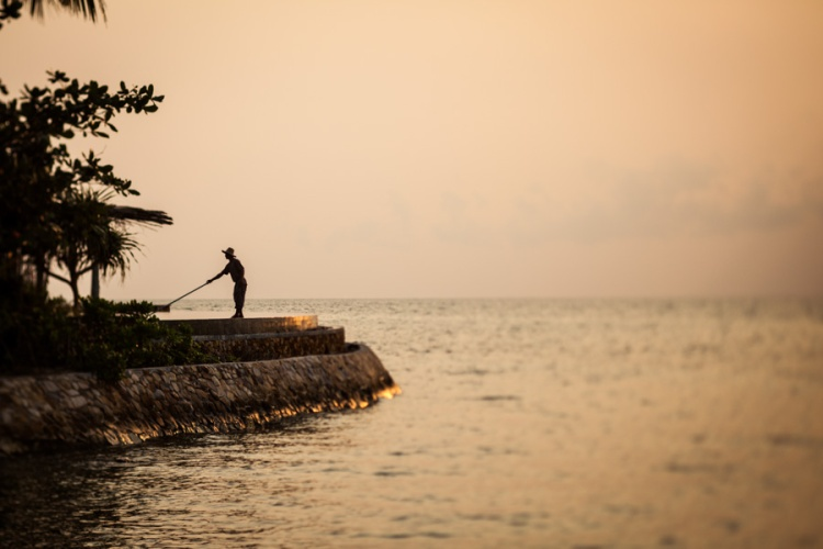 A worker cleans an infinity pool at dawn at the exclusive Song Saa resort, on its own private island off the coast of southern Cambodia (silhouette).