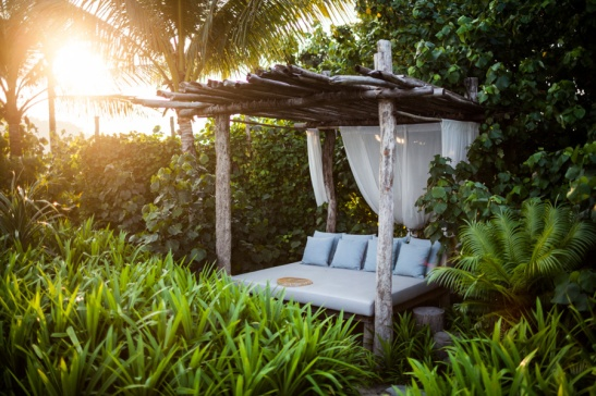 A bed sits in a garden grove at sunset, at Song Saa resort, on its own private island off the coast of Sihanoukville, Cambodia.