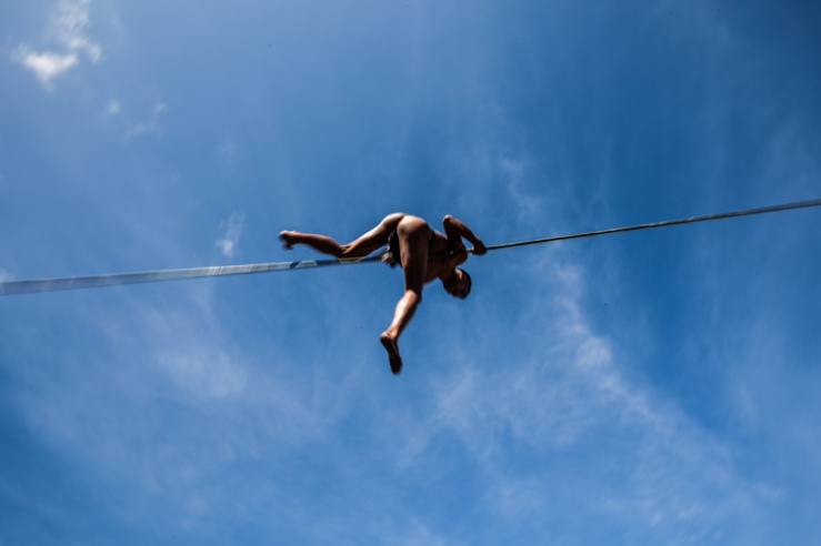 A tribesman at the Hornbill Festival in Nagaland, India, hangs suspended from a bamboo rope (blur).