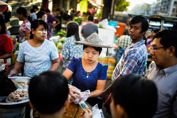 A young Burmese street seller at a crowded market in downtown Yangon, Myanmar.