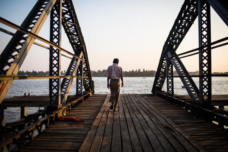A man walks along a pier toward the Yangon River in downtown Yangon, Myanmar.