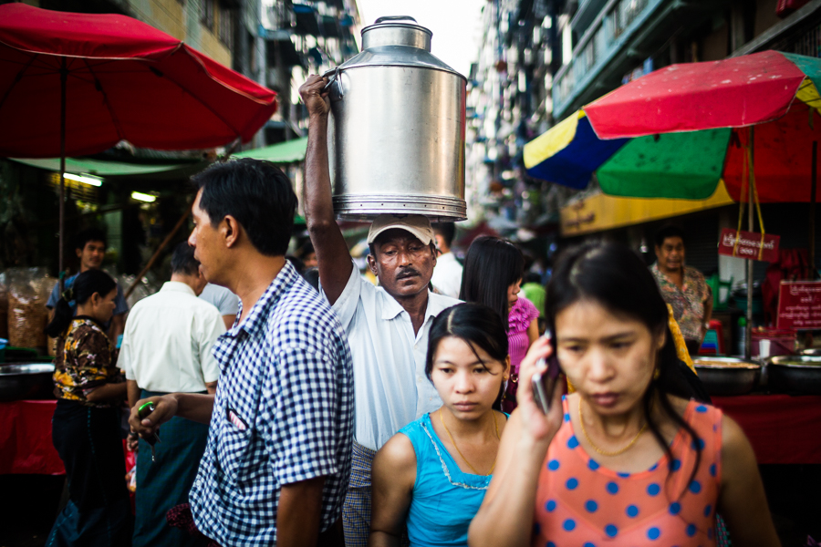 A man carries a jug of water through the streets of Yangon, Myanmar.