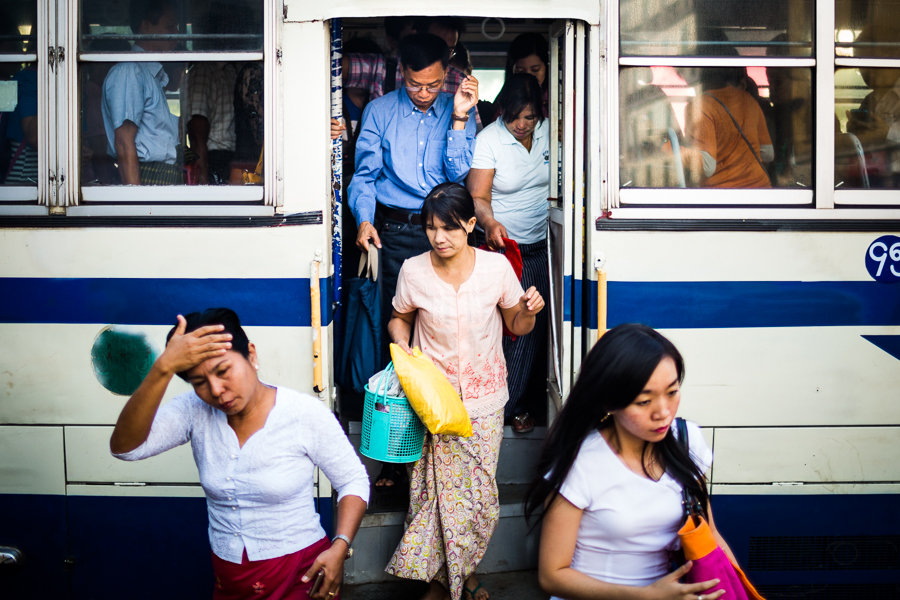 Locals exit a small bus in downtown Yangon, Myanmar.