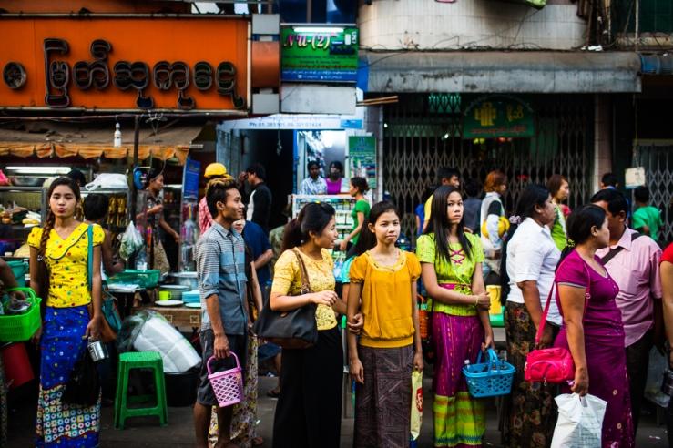 Burmese men and women wait for the bus in downtown Yangon, Myanmar.