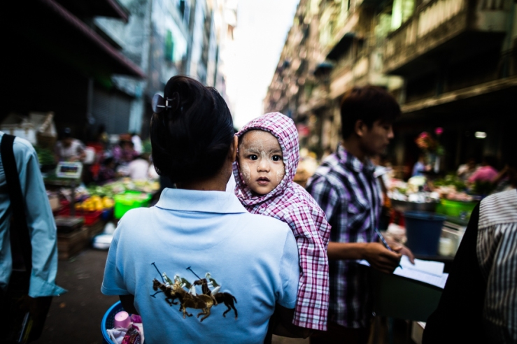 A young child is carried through a street market in downtown Yangon, Myanmar.
