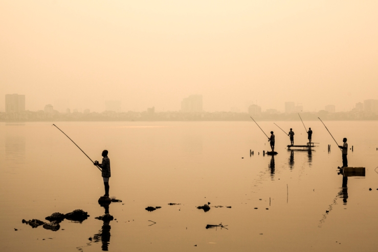 Fishermen at sunset on West Lake in Hanoi, Vietnam.
