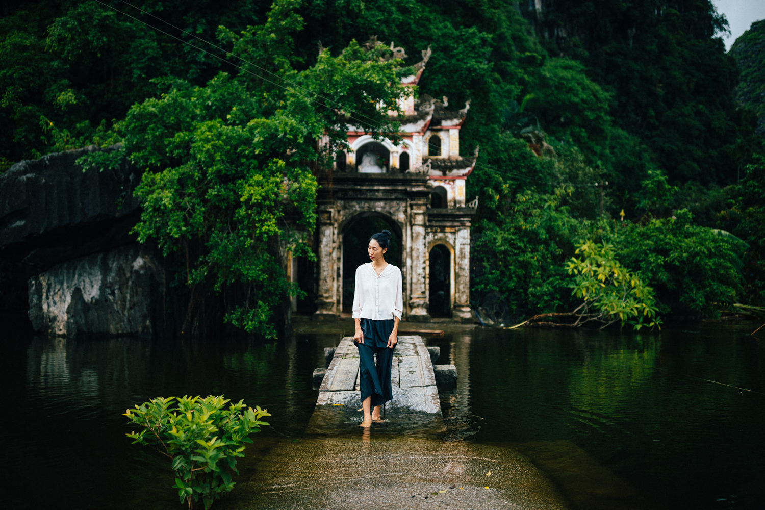 A young woman and a small temple in Ninh Binh, Vietnam.