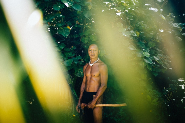 A portrait of a Chamorro seafarer, holding an axe he uses to build canoes.